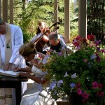 Witnesses sign the register beneath the pergola while musicians play.